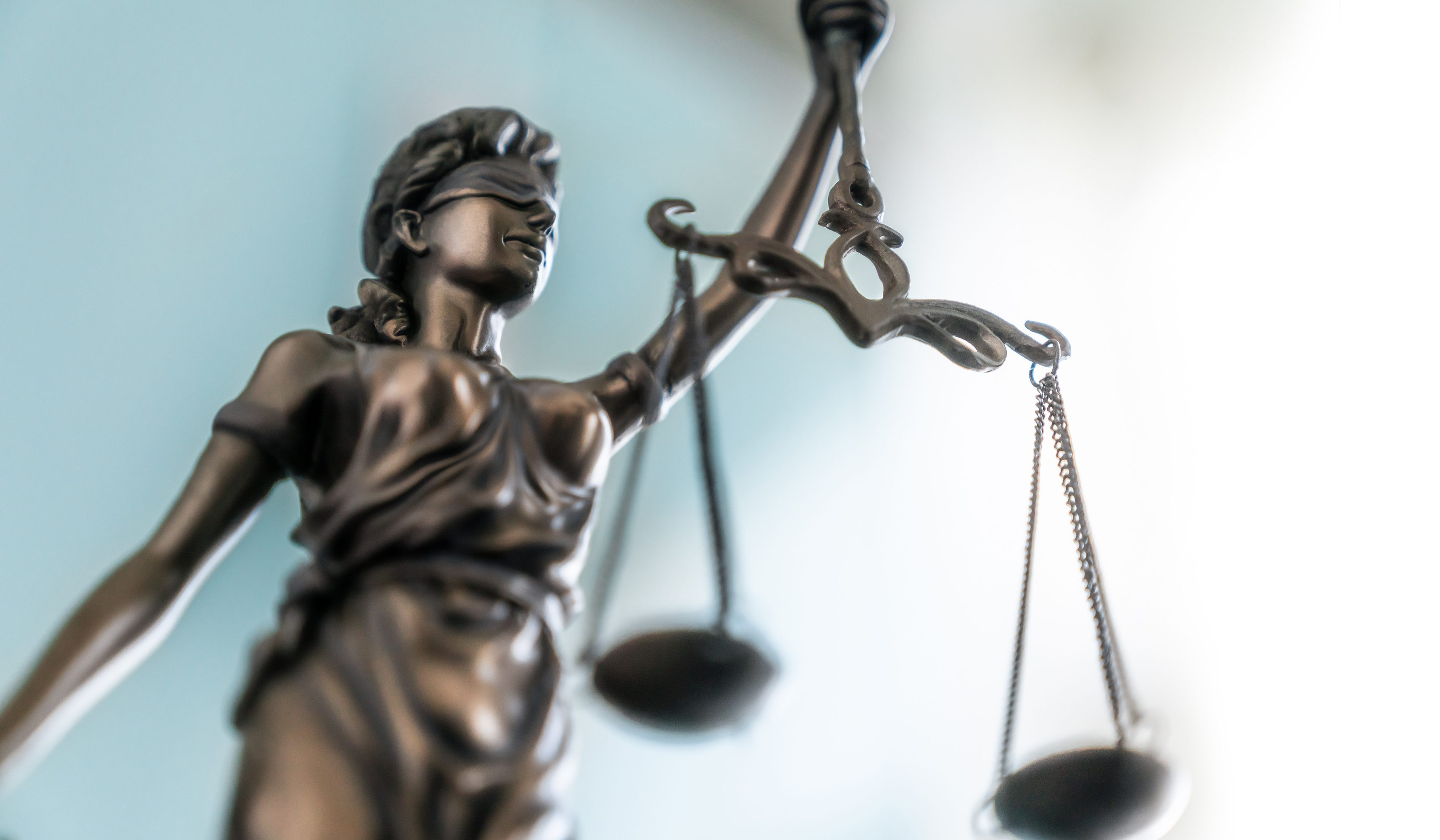 A statue of Justice wearing blindfold and brandishing a scale, symbolizing the law and justice.